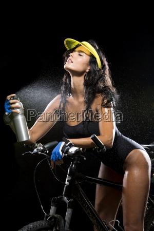 woman with mountain bike refreshing herself