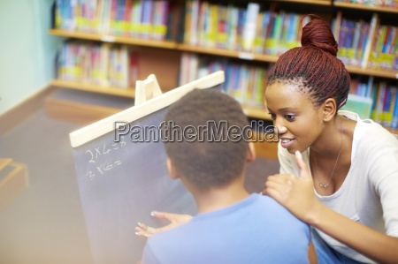 young woman doing maths with boy