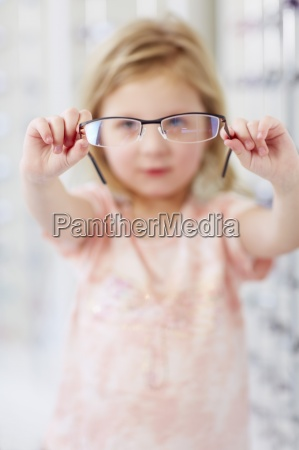 girl at the optician holding glasses