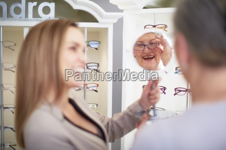 optician counseling senior woman in shop