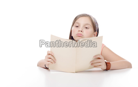 preteen girl reads a book on