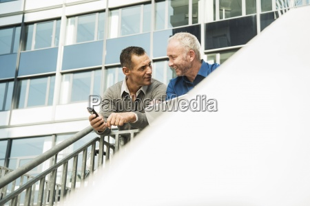 two businessmen outside office building using