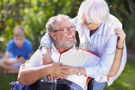 senior woman embracing husband in wheelchair
