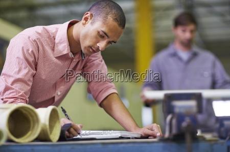 man in workshop writing next to