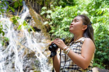 girl using binoculars in forest