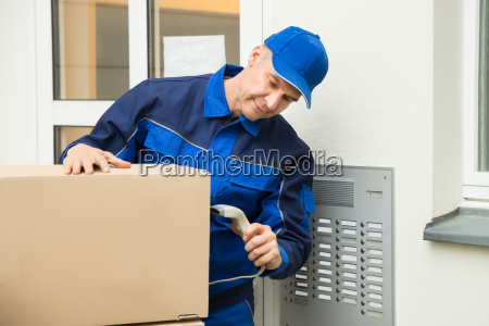 delivery man scanning cardboard boxes with