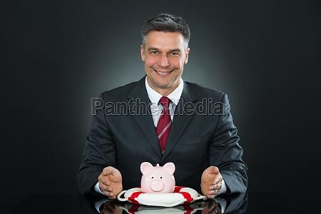 mature businessman protecting piggybank with lifebelt