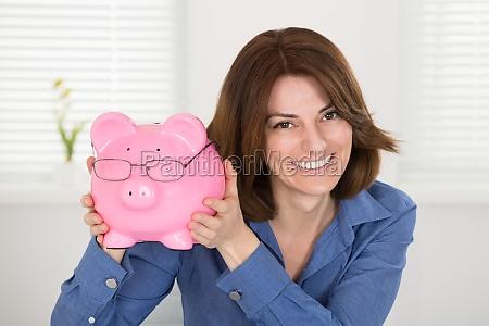 happy businesswoman holding piggybank