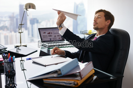 bored white collar worker throwing paper