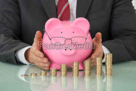 businessman covering piggy bank with stacked