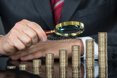 close up of businessman examining coins