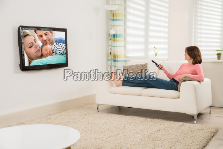 woman watching television while lying on