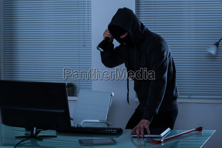 robber with flashlight in office