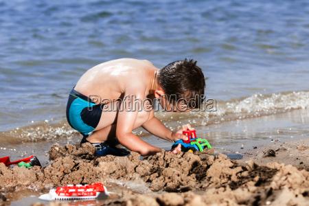 little boy in blue sea playing
