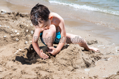 little boy in blue sea playing