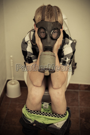 child in gas mask sitting on