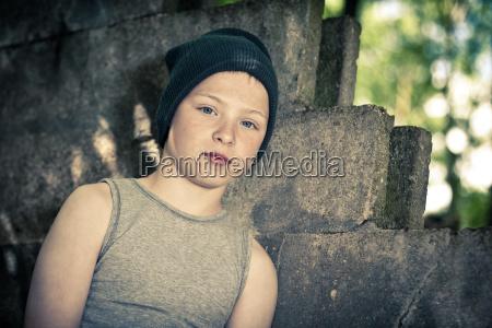 serious boy in hat sitting near