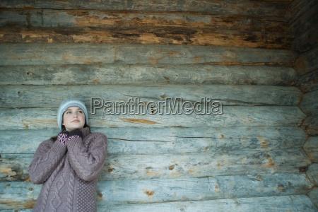 menina adolescente vestindo roupas quentesencostado cabana