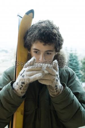 menino adolescente com esquis que bebem