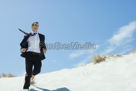 businessman running across sand dune low
