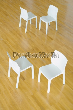 two pairs of chairs on hardwood