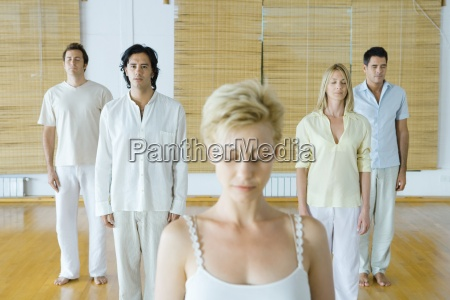 group of adults standing meditating all