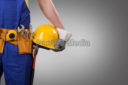 construction worker holding helmet on gray