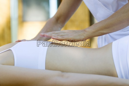 therapists hand hovering over patients back