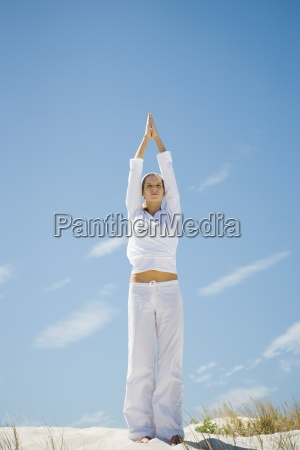 young woman standing on dune exercising