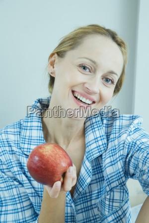 woman wearing pajamas holding up apple
