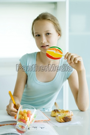 girl eating sweets and doing homework