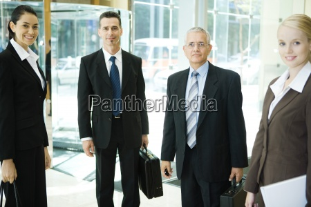business associates standing in lobby smiling