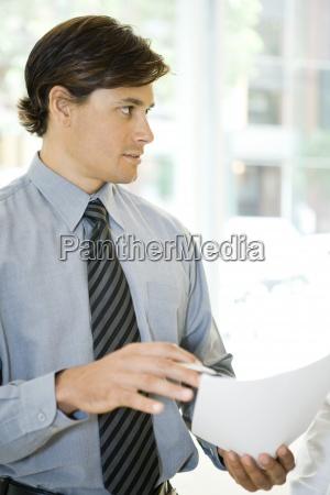 businessman holding document looking away waist