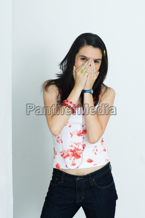 teenage girl covering face with hands