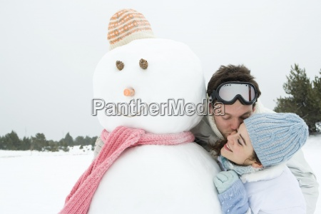 young couple next to snowman man