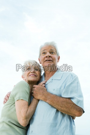 senior couple embracing and looking away