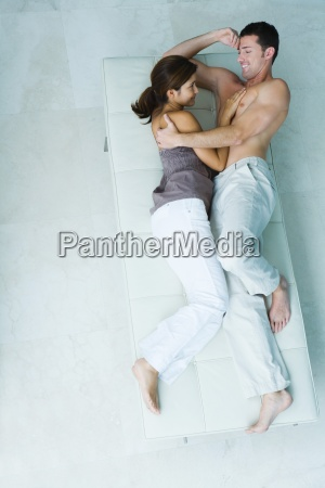 couple lying on chaise longue together