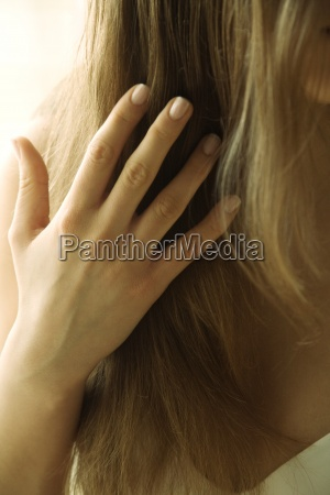 young woman touching hair cropped view
