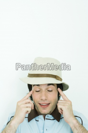 young man wearing hat pointing at