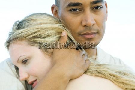 couple embracing man looking at camera