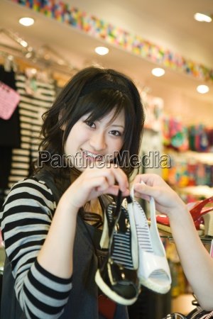 young woman in shoe store holding