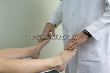 doctor examining patients feet