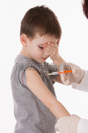 doctor giving a child injection in