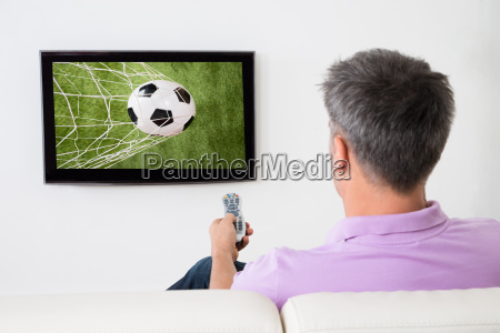 man watching soccer game on television