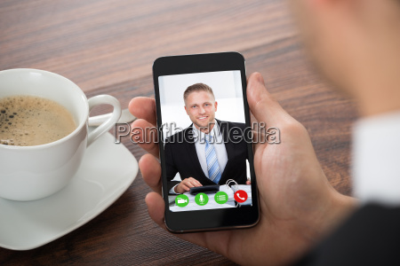 businessman videochatting with colleague on mobile