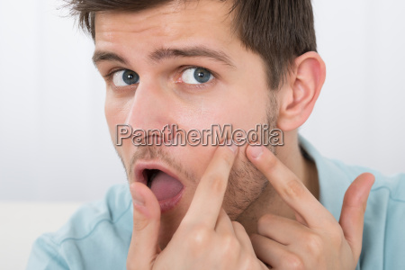 man looking at pimple on forehead