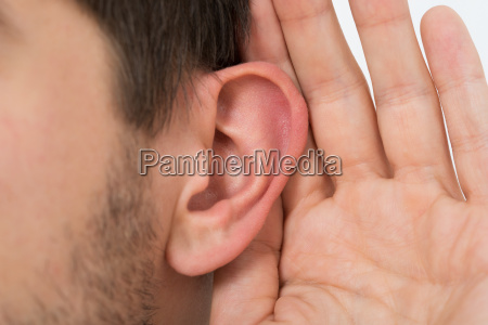 person trying to hear with hand