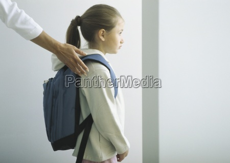 womans hand on shoulder of girl