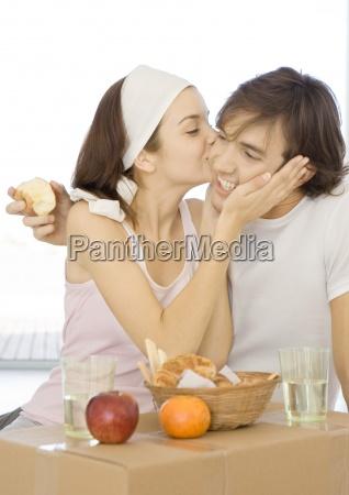 couple having breakfast on cardboard box