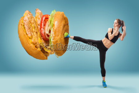 fit young energetic woman boxing hamburger